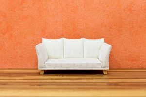 A white sofa in front of an orange wall.