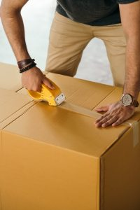 Man taping a cardboard box as packing is something movers help you with besides moving.
