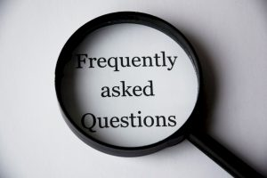 There is a magnifying glass showing the inscription Frequently asked Questions, since asking questions is crucial when buying a home long distance.