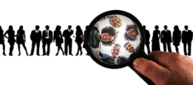 A group of people observed trough a looking glass symbolizing focus on employees.