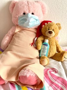 Teddy bears with a protective face mask and a hand sanitizer.
