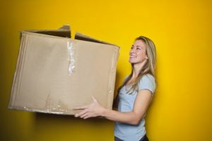 A woman in front of a yellow wall holding a box